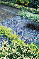 Creative use of variety of different ornamental grasses and reflective blue stones in a low maintenance mulch planting, colored blue marbles, patio, Santolina in yellow flowers, and Hakon grass, Phalaris ribbon grass, in a yellow gold and blue color theme