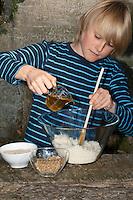 Kind, Junge macht Pesto aus Walnüssen, Sonnenblumenkernen, Olivenöl und Parmesankäse selbst, Olivenöl wird hinzugegeben, Walnuss, Walnuß, Wal-Nuss, Wal-Nuß, Nüsse, Ernte, Juglans regia, Walnut, Noyer commun, Sonnenblumen, Helianthus, Sunflower
