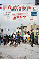 Nathan Schroeder and team leave the ceremonial start line with an Iditarider at 4th Avenue and D street in downtown Anchorage, Alaska during the 2015 Iditarod race. Photo by Jim Kohl/IditarodPhotos.com