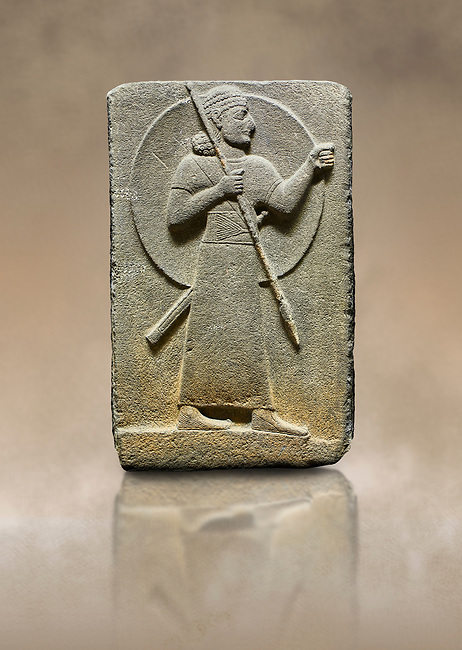 Photo of Hittite relief sculpted orthostat stone panel of Royal Buttress. Basalt, Karkamıs, (Kargamıs), Carchemish (Karkemish), 900-700 B.C.  Warrior.  Anatolian Civilisations Museum, Ankara, Turkey.<br /> <br /> The figure with a long dress, a thick belt and curly hair has a large egis on his back. The figures carries a spear in his right hand and a long sword at his waist.  <br /> <br /> Against a brown art background.