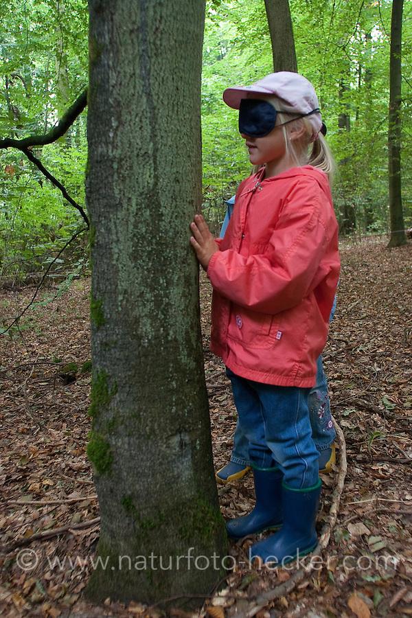 Mädchen fühlt Baum-Rinde, Waldspiel mit verbundenen Augen zum Kennenlernen von Rinde, Rindenspiel, Kinder im Wald, Kinder erleben die Natur im Wald, Walderlebnistag, Schulkinder bei einer Waldexkursion, Exkursion, Kinder sammeln im Wald Blätter, Äste, Zapfen, Früchte, Grundschulklasse, Schulklasse