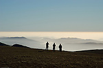 Three mountaineers silhouetted, taking in the view at the top of High Street. The Lake District, Cumbria, UK