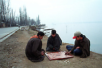Kashmiri boys play carrom at the bank of Dal lake, Srinagar, Jammu and Kashmir