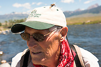 Wayne Lehmann, of Bozeman, Montana, is covered with stoneflies while fishing on the Madison River.