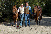 A cowboy couple walk their horses after a romantic ride