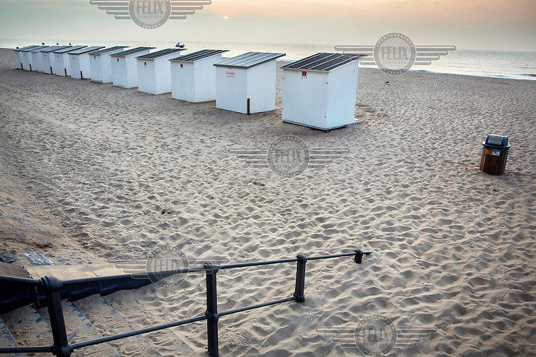 Beach huts on the sand.
