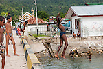 Kaimana, West Papua, Indonesia; local boys jumping and diving off the pier to play in the water