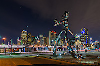 Traveling man at night in downtown Dallas at the train station but no train with the city skyline in the background. This area of Deep Ellum has been revitalized and the traveling man scuplture is part of that it is suppose to represent the railroad history of this area. There are three scupture one with just the head coming up from the ground as the birth, the walking man, and the waiting on the train banjo playing man. All three statues are made of polish metal, with rivets to represent the railroad history.