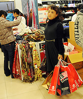 A woman carrying bags of merchandise at a department store in Chengdu, China. Economic conditions had been greatly improved both domestically and externally as China's economy consolidates its recovering trend. According to the figures from the National Bureau of Statistics (NBS), China's consumer price index (CPI), a main gauge of inflation, rose 0.6 percent year on year in November..05 Dec 2009.