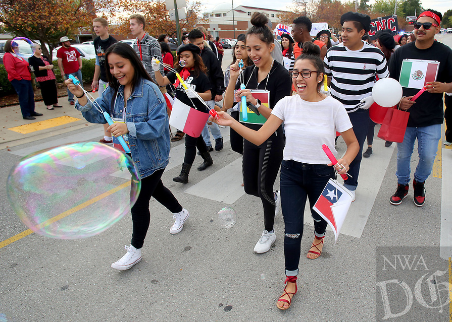 NWA Democrat-Gazette/DAVID GOTTSCHALK  Jessica Cenobio (from left), Abril Guerra and Shelby Saldivar, all seniors at Springdale High School, make bubbles Friday, October 20, 2017, as they walk with the Language Classes from the school in the Springdale High School Homecoming 2017 Parade. The parade was followed by an assembly.