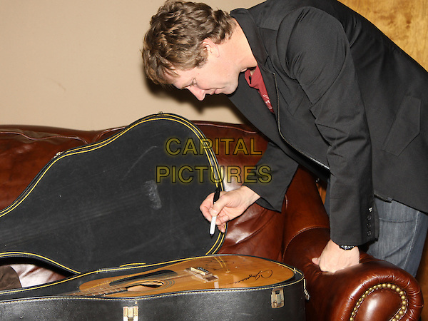 CRAIG MORGAN.autographed a guitar to be auctioned off for charity backstage before his concert at Cowboys Country Club, Kennesaw, GA, USA, November 20th 2009..half length case profile signing autographing .CAP/ADM/DH.©Dan Harr/AdMedia/Capital Pictures.