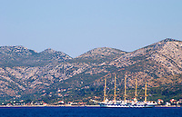 The Peljesac peninsula and Sveti Ilija mountain with a big sailing cruise ship schooner SPV Royal Clipper with five masts on the sea water Korcula Island. Korcula Island. Dalmatian Coast, Croatia, Europe.
