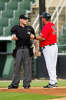 Home plate umpire Travis Godec explains a call to Kannapolis Intimidators manager Tommy Thompson (39) during the South Atlantic League game against the Greenville Drive at CMC-Northeast Stadium on June 29, 2013 in Kannapolis, North Carolina.  The Intimidators defeated the Drive 9-3 in the completion of the game that began on June 28, 2013.   (Brian Westerholt/Four Seam Images)
