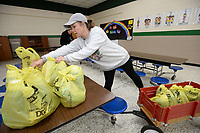 Lori Gaither, a literacy aide at Greenland Elementary School, gathers bags Saturday, March 21, 2020, during a giveaway of food and household items at the school. The school, along with Lincoln, Gravette and Pea Ridge, partners with Essentials Outreach and Tyson Foods to provide necessary items to families in its district on third Saturday of the month. After serving 27 families in its first month last month, Greenland gave items to 271 individuals on Saturday. Visit nwaonline.com/200322Daily/ for today's photo gallery.<br /> (NWA Democrat-Gazette/Andy Shupe)