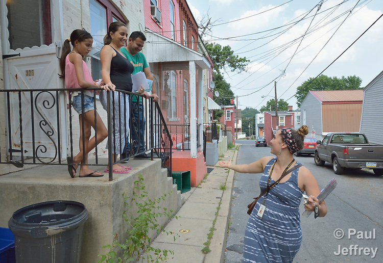 Evi Long (right), a Cuban/Haitian resettlement case manager with Church World Service, says goodbye to Yureisy Ceballos Pendones and Eliocer Curino and their daughter Elianys outside the Cuban refugee family's home in Lancaster, Pennsylvania. <br /> <br /> Church World Service resettles refugees in Pennsylvania and other locations in the United States. <br /> <br /> Photo by Paul Jeffrey for Church World Service.