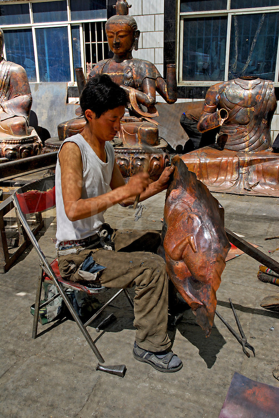 Tibetan coppersmith hammers a panel to be used in creating a Buddha statue at the Dropenling Handicraft Center for Tibetan arts and crafts, Lhasa, Tibet.