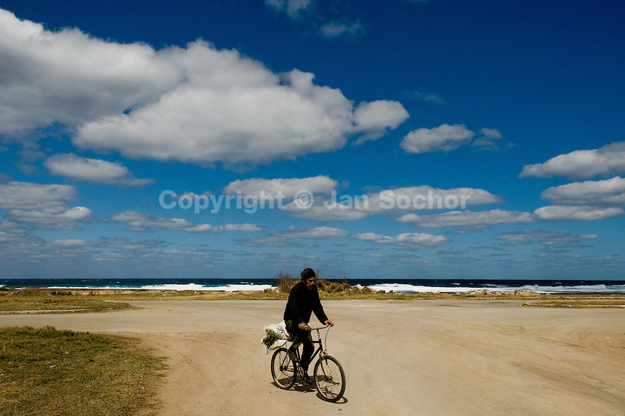 A Cuban man rides a bicycle on the dusty road along the sea, carrying vegetables from his garden to his home in the Eastern Havana, Cuba, 5 February 2009. About 50 years after the national rebellion, led by Fidel Castro, and adopting the communist ideology shortly after the victory, the Caribbean island of Cuba is the only country in Americas having the communist political system. Although the Cuban state-controlled economy has never been developed enough to allow Cubans living in social conditions similar to the US or to Europe, mostly middle-age and older Cubans still support the Castro Brothers' regime and the idea of the Cuban Revolution. Since the 1990s Cuba struggles with chronic economic crisis and mainly young Cubans call for the economic changes.