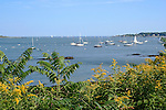 Harbor in Maine with boats anchored and lighthouse in background