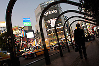 A male office worker or salaryman walks under some arches near Hachiko crossing in Shibuya, Tokyo, Japan. Friday, January 21st 2011