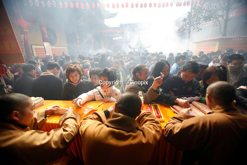 Worshippers make donations to have their names posted on the temple walls at the Jade Buddha Temple in Shanghai, China. The first day of the Chinese New Year is one of the most auspicious days in the year to offer incense and prayers..18 Feb 2007