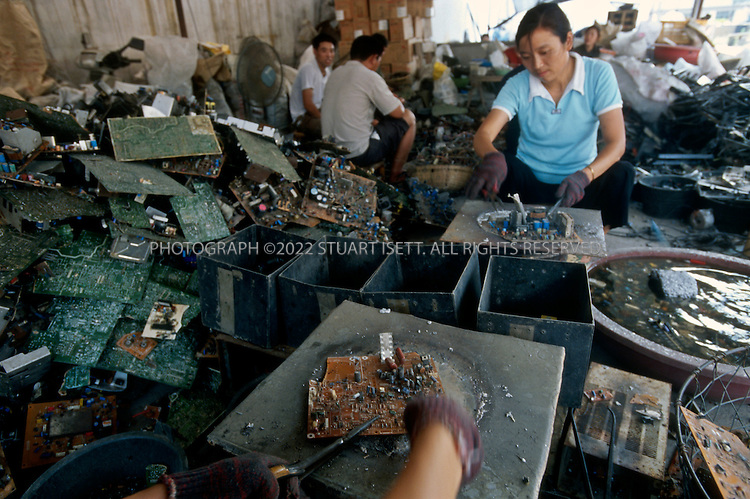 7/2/2005--Taizhou, Zheijiang Province, China..At a small factory workers melt down computer parts....The eastern Chinese port city of Taizhou has now become the center for much of the illegal trade in e-waste (computer waste). 24 hours a day ships arrive in the city?s harbor carrying cargo of waste, including millions of computer parts. These parts flow out of the port in trucks into the city and hinterland where hundreds of tiny work shops break down the parts, melting off the precious metals and using acids to separate gold from circuits boards, mobile phones, monitors and other computer parts. Neighborhoods are filled with the noxious and toxic fumes of this unregulated industry and thousands of men, women and children are exposed to a toxic cocktail of fumes and dust released. .Photograph By Stuart Isett.All photographs ©2005 Stuart Isett.All rights reserved.
