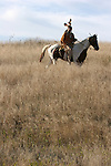 A Native American Indian man riding horseback scouting for enemies or hunting for food in the prairie of South Dakota