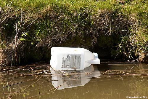 Een lege verpakking van een bestrijdingsmiddel (met Andreas-kruis) drijft op het water. An empty container of a pesticide (with Andreas cross) floats on the water.