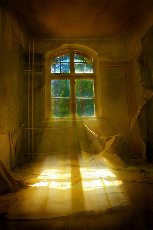 A derelict building with light shining through a window