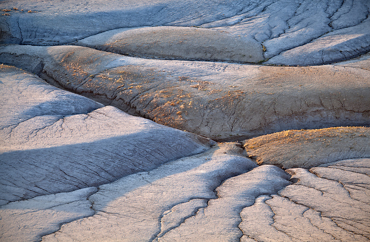 An aerial-like view of light and shadows dancing across patterns and mounds in the Mancos Shale geologic formation in the Caineville Badlands in southern Utah, USA