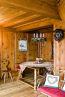 A traditional cuckoo clock hangs above a rustic chair, originally a chariot seat, in this dining room with salvaged wood panels