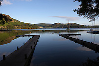 Boat jetties stretch out over the calm waters of Sharrow Bay, Ullswater, Lake District, Cumbra