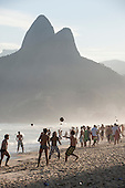 Rio de Janeiro, Brazil. Two brothers (Dois Irmaos) mountain and many football mad Brazilian men playing football on the beach in the afternoon.