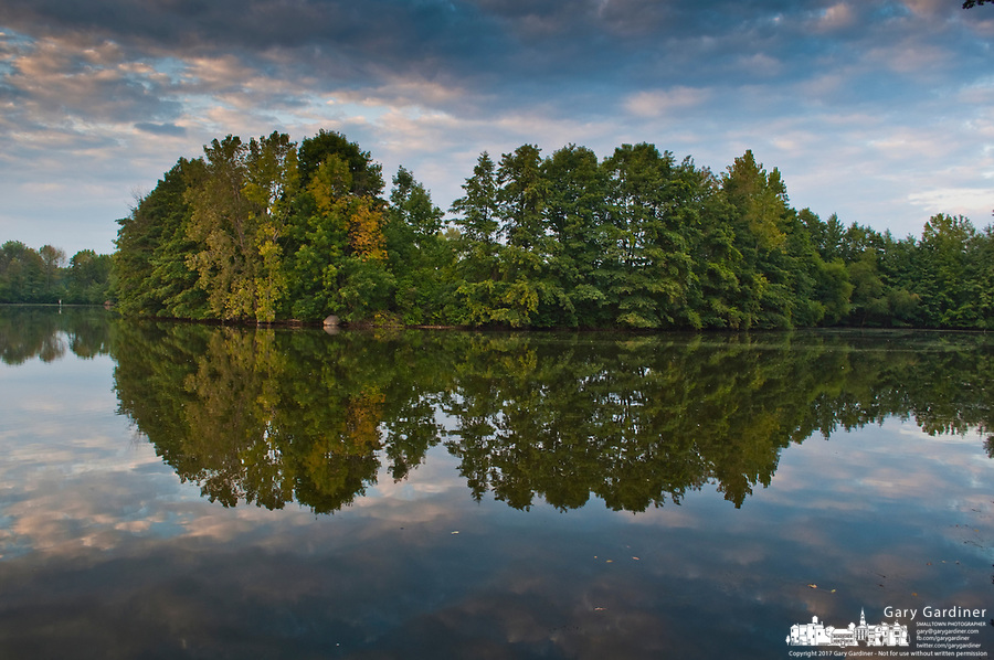 Trees lining Schrock Lake at Sharon Woods Metro Park in Columbus, Ohio, are reflected at sunset in the  smooth water of the small lake used for fishing by park goers.