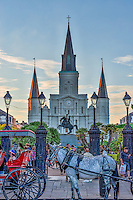 Jackson Square in the French Quarter in New Orleans as people enjoy the view of the city and the horse cariages wait for a fare. This is one of the oldest area of the city and is considerd a historic landmark.