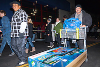 "An unknown man walks out of the Costa Mesa Best Buy on the morning of Black Friday with a cart holding a 42"" TV and a Best Buy bag.  Behind him is a line of Occupy Orange County Irvine and Santa Ana protestors, marching in front of the store's entrance."
