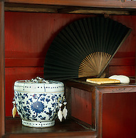 An open fan and a blue and white decorated pot on a Chinese shelf in the living room