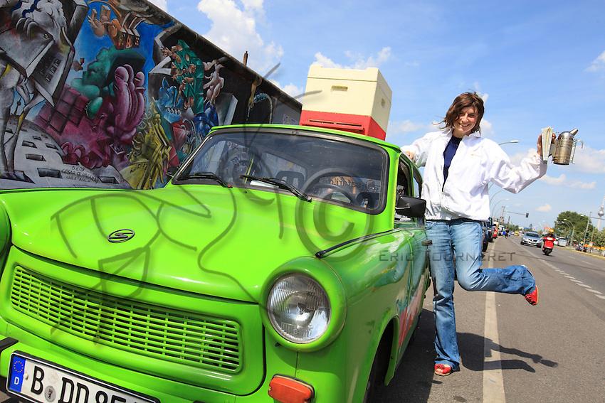 Erica Mayr, jeune femme de 37 ans pose avec une Trabant, une ruche et un enfumoir près de ce qui reste du mur de Berlin près de Warschauer Strabe.///Erica Mayr, 37 years old, posing with a Trabant, a hive and a smoker close to what is left of the Berlin Wall near Warschauer Strabe.