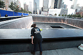 A volunteer cleans the names of the dead along the North Pool at the September 11th Memorial at the World Trade Center site in New York on September 11, 2011..Credit: Jefferson Siegel / Pool via CNP