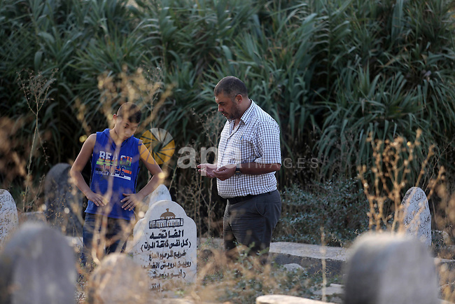 Palestinians pray over the graves of relatives in a cemetery, on the Muslim holiday of Eid al-Adha or the feast of sacrifice, in the West Bank City of Ramallah on September 24, 2015. Muslims across the world are celebrating the annual festival of Eid al-Adha, or the Festival of Sacrifice, which marks the end of the Hajj pilgrimage to Mecca and in commemoration of Prophet Abraham's readiness to sacrifice his son to show obedience to God. Photo by Shadi Hatem