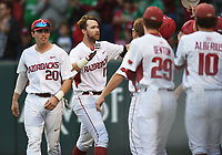 NWA Democrat-Gazette/ANDY SHUPE<br />Arkansas left fielder Luke Bonfield (center) is congratulated at the plate by teammates Friday, March 17, 2017, after hitting a 2-run home run scoring Chad Spanberger during the first inning against Mississippi State at Baum Stadium in Fayetteville. Visit nwadg.com/photos to see more photographs from the game.