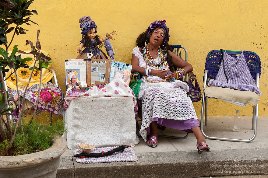 Havana, Cuba; a street performer named Adelaida takes a nap on the side of the street, she is dressed up so tourist will pay her to take her photo