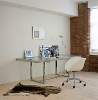 A chrome and glass table is used as a desk in one corner of this large open-plan space