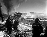 U.S. Marines move forward after effective close-air support flushes out the enemy from their hillside entrenchments.  Billows of smoke rise skyward from the target area.  Hagaru-ri.  December 26, 1950.  Cpl. McDonald.  (Marine Corps)<br /> NARA FILE #:  127-N-A5439<br /> WAR &amp; CONFLICT BOOK #:  1432