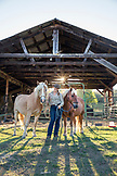 USA, Oregon, Willamette Valley, Clare Carver stands with her horses in front of the barn at Big Table Farms Winery, Gaston
