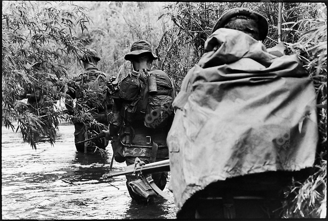 Members of an Americal (23rd ) Division wade through a stream while on a mission in II corps, near Quang Ngai, South Vietnam, November 1970