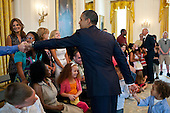 "July 5, 2011.""The President shakes hands with a wounded warrior and the child of a wounded warrior who had crept up behind him in the East Room. The President and the Vice President, seen in the background, often drop by when wounded warriors and their families are touring the White House."".Mandatory Credit: Pete Souza - White House via CNP"