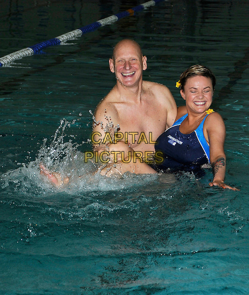 DUNCAN GOODHEW & GAIL PORTER.At a photocall for the Swimathon 2011 launch, Marshall Street Leisure Centre, London, England, UK, .11th January 2011..half length blue swimming costume swimsuit in water pool lifting carrying smiling yellow flowers in hair full foot splashing  eyes shut .CAP/CAN.©Can Nguyen/Capital Pictures.
