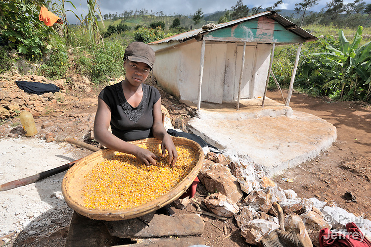 A woman winnows corn in the Haitian village of Foret des Pins.