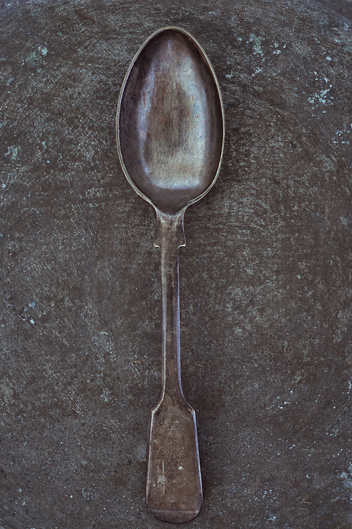 Antique tarnished silver teaspoon lying on tarnished metal