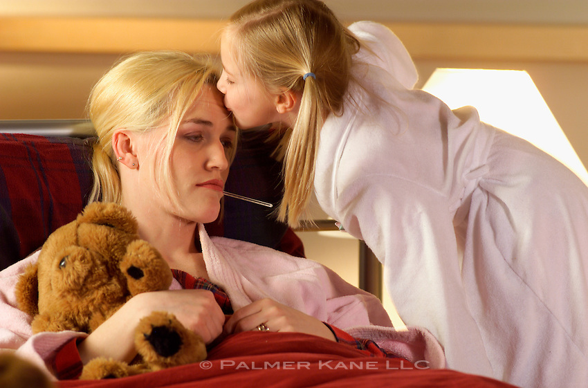 Young daughter caring for mother sick in bed
